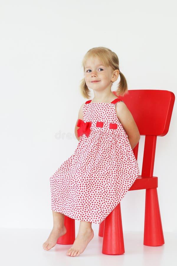 Babymeisje op rode stoel stock fotografie