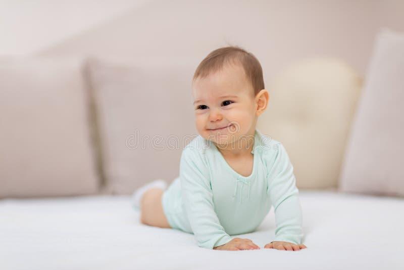 Babymeisje op wit bed stock afbeeldingen