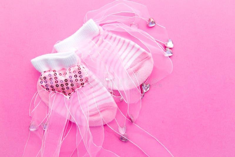 Babymeisje - roze en witte sokken met kant op roze achtergrond royalty-vrije stock afbeelding