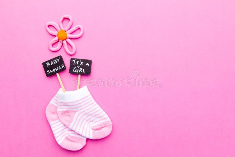 Babymeisje - roze en witte sokken op roze achtergrond met Babydouche en het ` s de tekens van een Meisjesbord stock fotografie