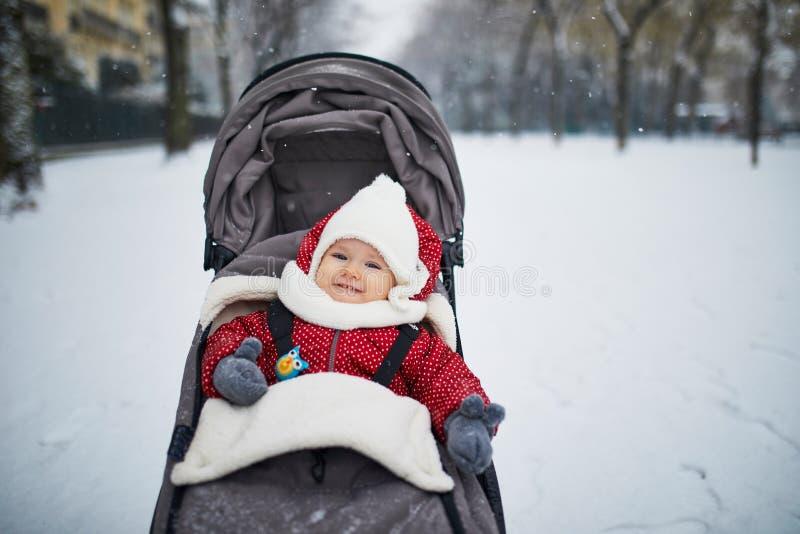 Babymeisje in wandelwagen in Parijs op een dag met zware sneeuw stock afbeeldingen