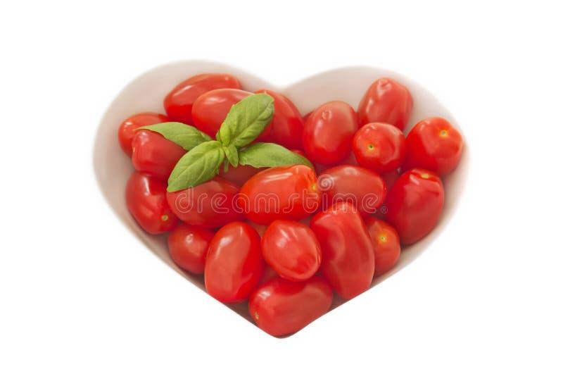 Babypflaume tomates in einem Herzen formten Schüssel lizenzfreie stockfotografie