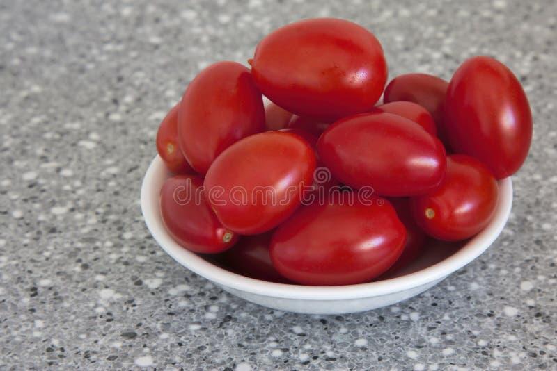 Babypflaume tomates in einem Herzen formten Schüssel lizenzfreie stockfotos