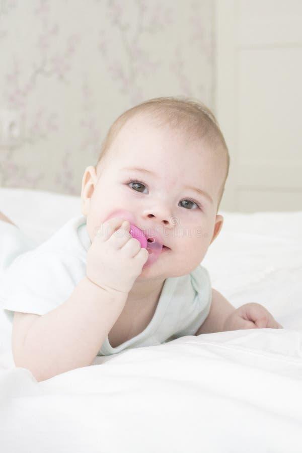 Babyporträt-Nahaufnahmevertikale Das Gesicht des Babys ist 6 Monate alte und liegt auf seinem Magen und zieht den Nippel in seine lizenzfreies stockbild