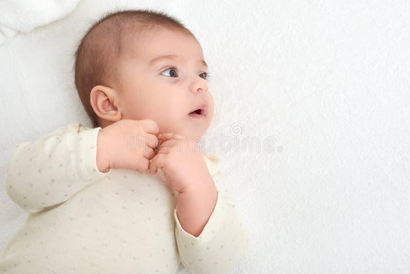 Babyporträtlüge auf weißem Tuch im Bett lizenzfreie stockbilder
