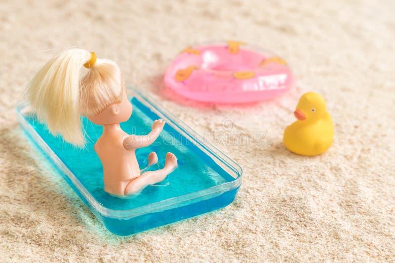 Babypuppe, die im Kinderswimmingpool nahe bei aufblasbarem Poolfloss und Gummiente auf dem minimalen kreativen Sommer des Strande stockbilder