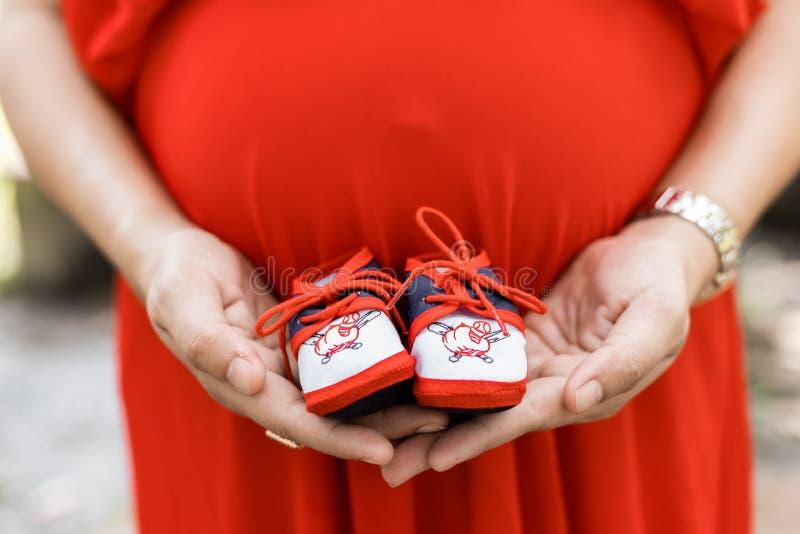 Babyschoen op buik stock foto's
