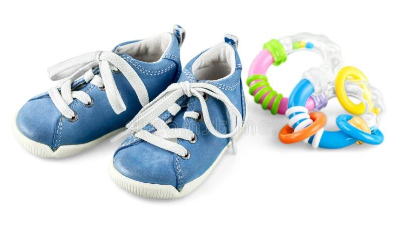 Babyschoenen en rammelaar op witte achtergrond worden geïsoleerd die royalty-vrije stock afbeeldingen