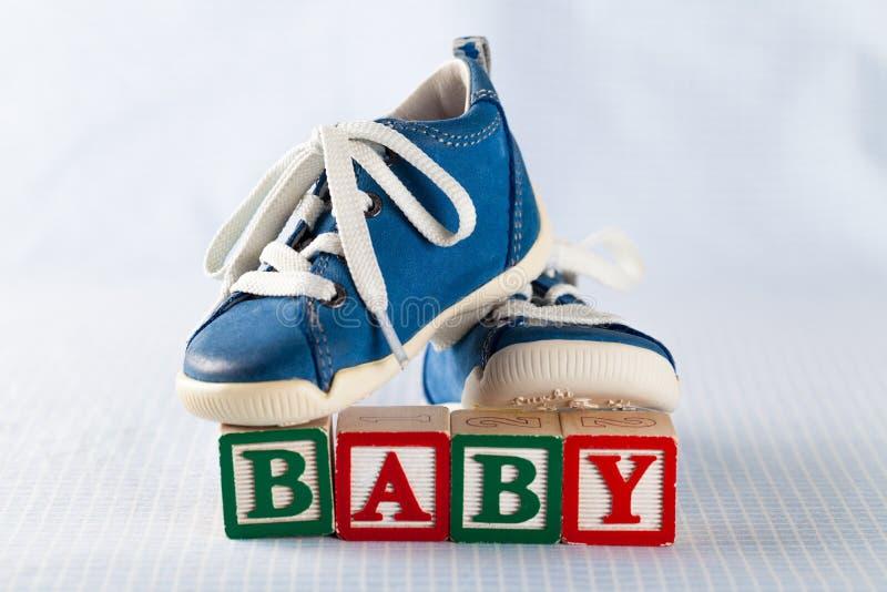 Babyschoenen en stuk speelgoed bakstenen met woordbaby royalty-vrije stock afbeelding