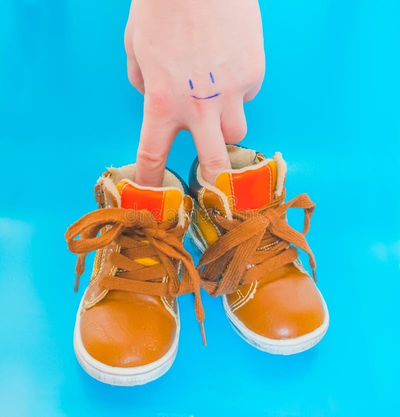 Babyschoenen op een blauwe achtergrond met een hand royalty-vrije stock foto