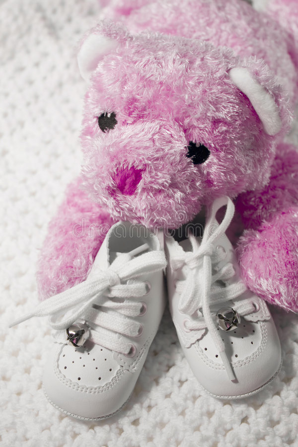 Babyschuhe und Teddybär lizenzfreies stockbild
