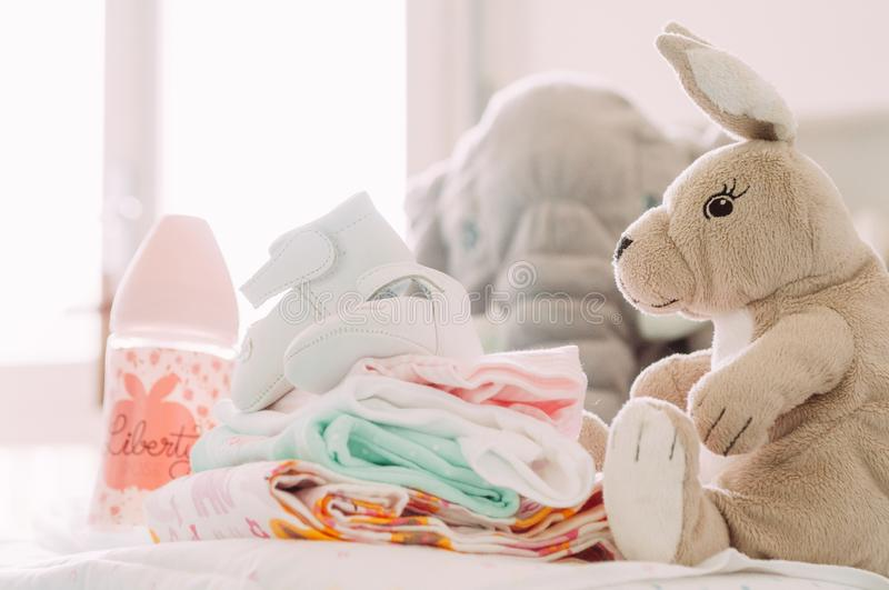 Babyshower gifts, shoes, puppets, clothes, feeding bottle, with modern chic style, standing on table indoors at home royalty free stock image