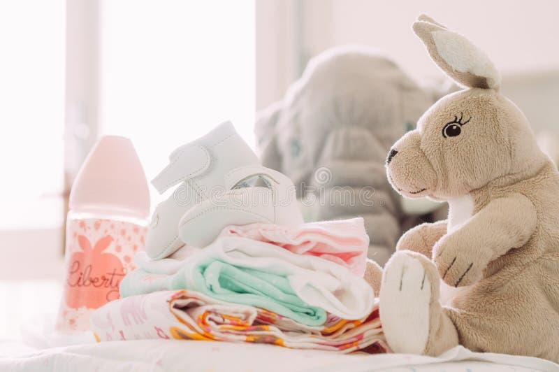 Babyshower prezenty, buty, kukły, odziewają, żywieniowa butelka z nowożytnym szyka stylem, stoi na stole indoors w domu obraz royalty free