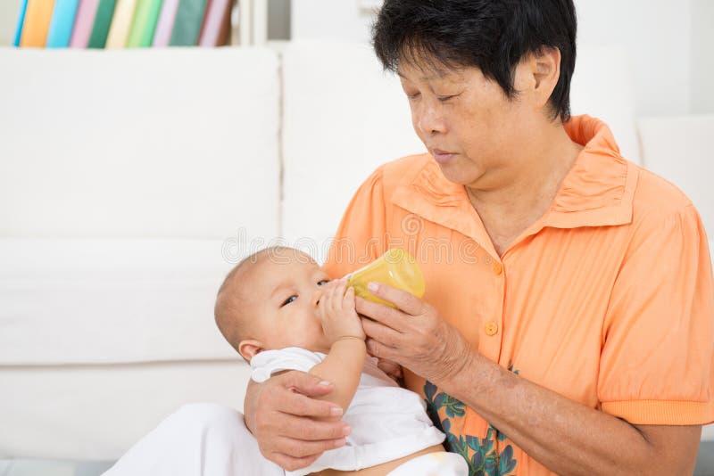 Babysitter bottle feeding baby royalty free stock photo