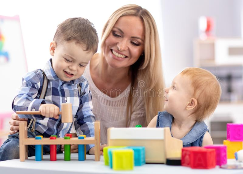 Babysitter and children playing together in nursery or day care centre stock images