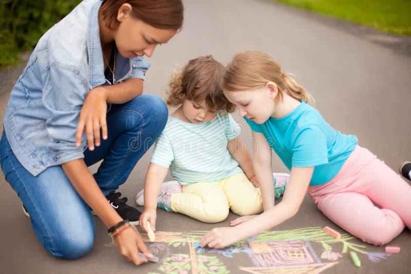 Babysitter eller dagisbegrepp Barn som drar med färg royaltyfri fotografi