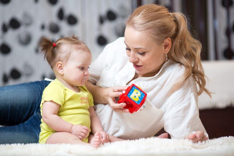 Babysitter en baby het spelen met stuk speelgoed kubussen thuis royalty-vrije stock foto's