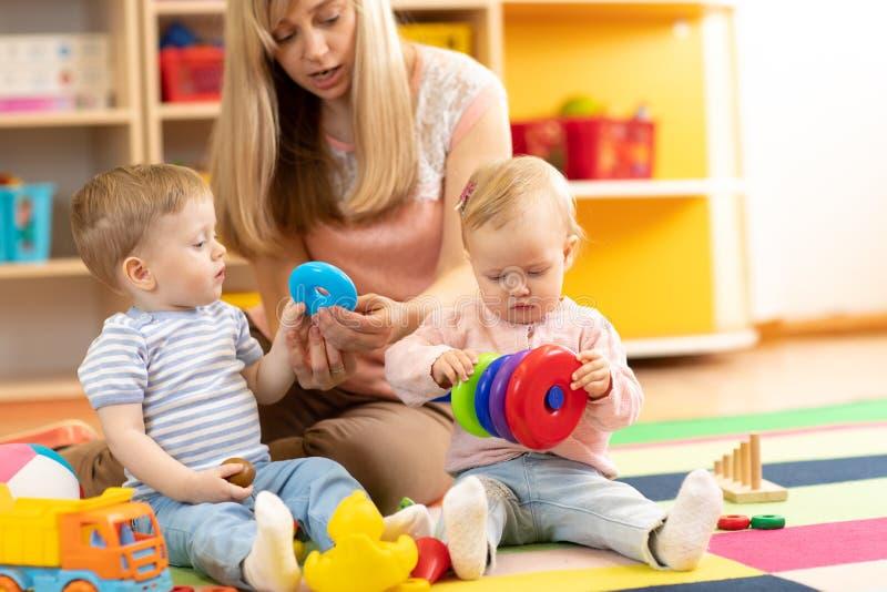 Babysitter en kinderenspel samen in kinderdagverblijf of opvangcentrum stock foto