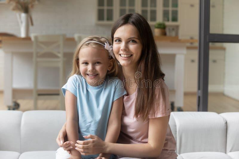 Babysitter en meisjes die op de bank zitten en naar de camera kijken royalty-vrije stock afbeelding