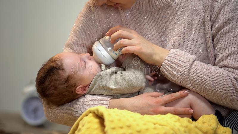 Babysitter feeding cute little child from bottle, artificial feeding accessories royalty free stock images