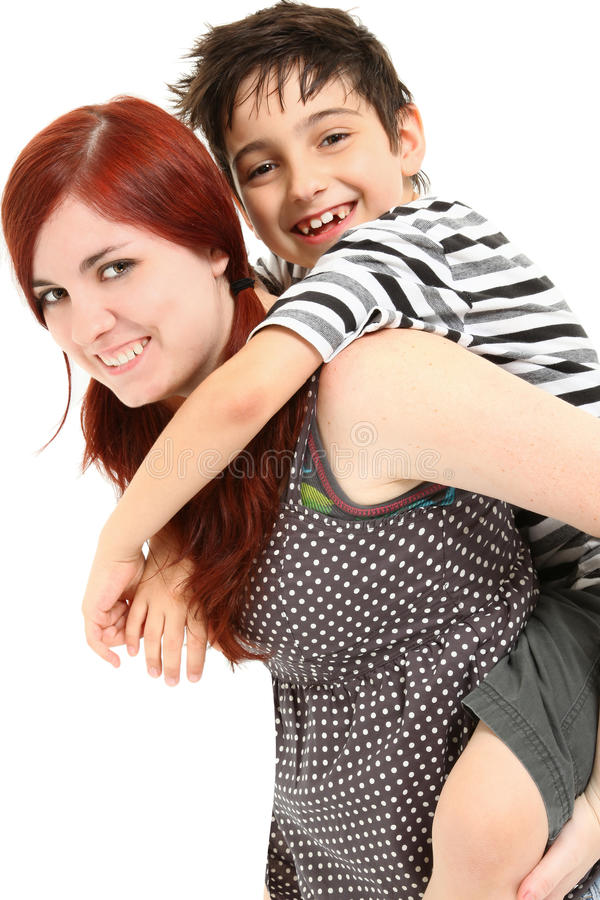Babysitter Giving Piggy Back Ride. Adorable 8 year old boy getting piggy back ride from babysitter over white background royalty free stock image
