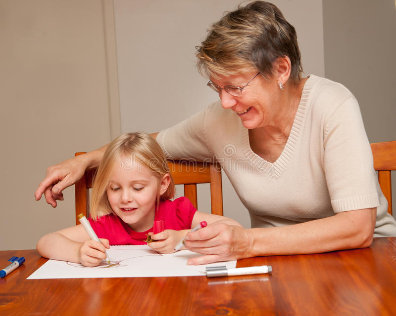 A babysitter helps a little girl with drawing stock images