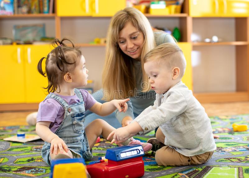 Babysitter plays with babies in nursery stock image