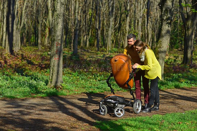 Babysitters walk with baby pram in park. Woman and man babysitters take care of little child. Responsibility and. Babysitters walk with baby pram in park. Woman stock photography