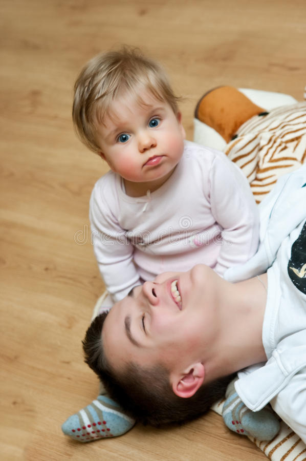 Babysitting. A teenage boy babysitting a baby girl royalty free stock photo