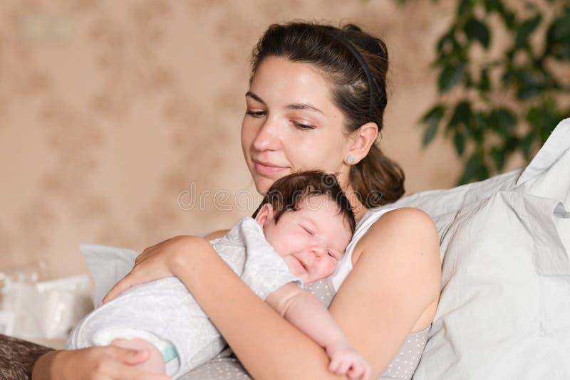 Babyslaap met mamma in haar wapens Mamma en Pasgeboren Baby Het mamma koestert binnen en houdt de pasgeboren baby in haar wapens, royalty-vrije stock afbeelding