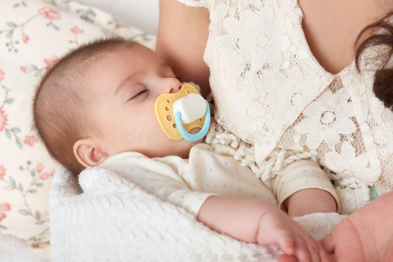 Babyslaap in moederhand, gelukkig moederschapsconcept stock fotografie