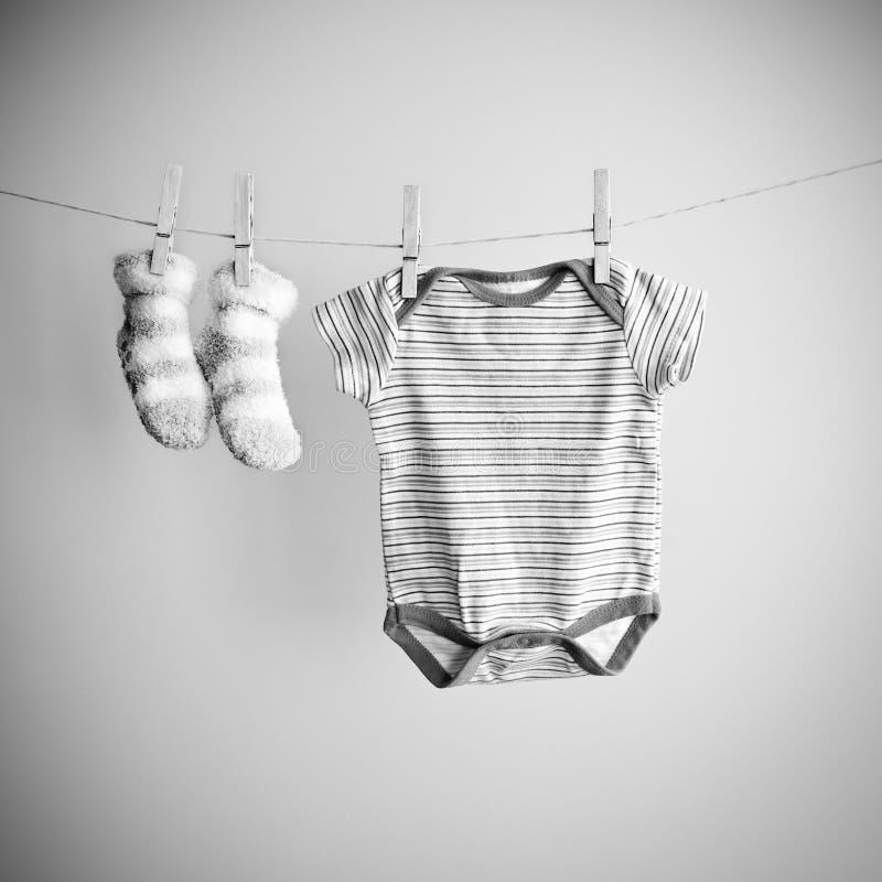 Babysokken en kleren die op de drooglijn hangen Achtergrond met babygoederen met exemplaarruimte Zwart-wit fotobeeld stock fotografie
