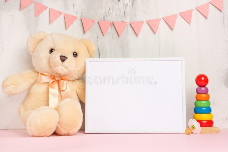Babyspeelgoed en kader op lichte muurachtergrond, voor ontwerp De douche van de baby royalty-vrije stock fotografie