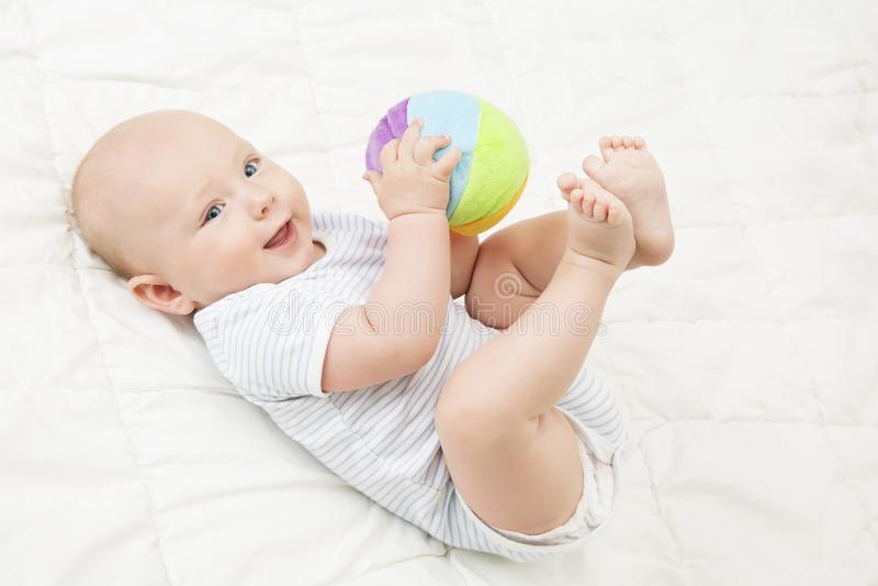 Babyspel Toy Ball die, Gelukkig Jong geitje op Rug liggen die Zacht Speelgoed spelen stock afbeeldingen
