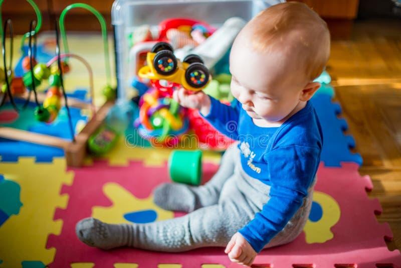 Babyspel in zijn ruimte met veel speelgoed royalty-vrije stock afbeelding