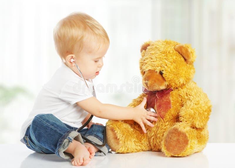 Babyspelen in artsenstuk speelgoed teddybeer en stethoscoop royalty-vrije stock afbeelding