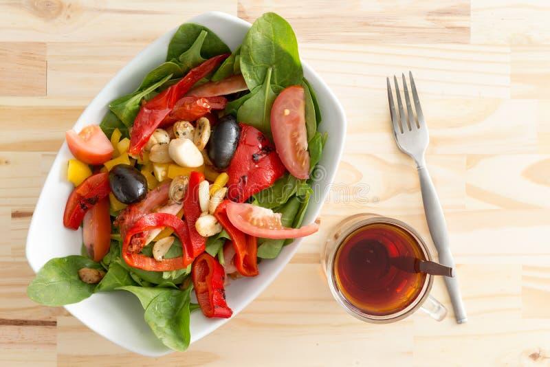 Babyspinatssalat mit Oliven, Pfeffern und Tomate stockfoto