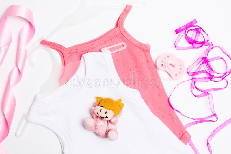 2 babysuits розовых и whie с игрушкой, pacifier и лентами Украшение детского душа на предпосылке whie стоковое фото
