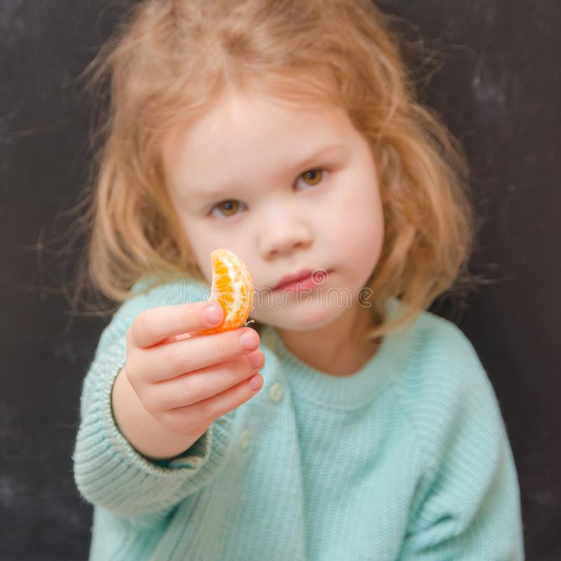 Babyvegetarier mit Mandarinenscheibe stockbild