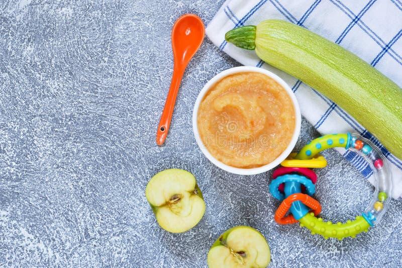 Babyvoedsel van 6 maanden Plantaardige puree van courgettes, zegels en aardappels op een concrete achtergrond stock afbeelding