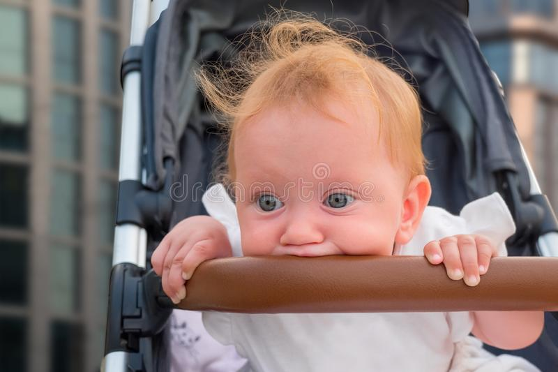 Babyvoertuigen Het zitten en het wachten op moeder Het leuke babymeisje wordt bored Jong geitje` s handen die bumper, familieconc royalty-vrije stock foto's
