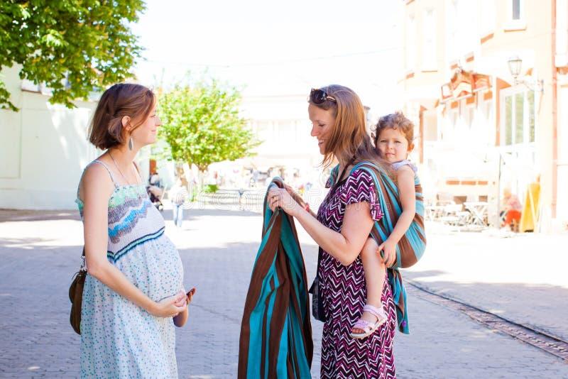 Babywearing顾问遇见怀孕的夫人室外在公园 库存图片