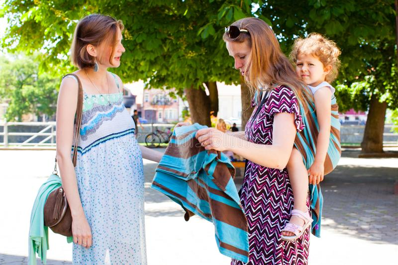 Babywearing mother shows sling to pregnant lady. Babywearing mother shows sling to her pregnant friend stock photography