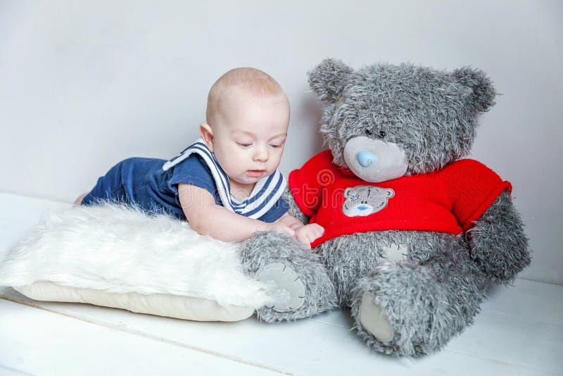 Babyzeeman op het hoofdkussen met teddybeer stock afbeeldingen