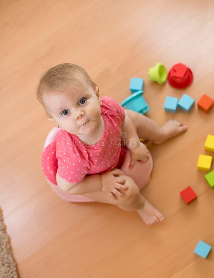 Babyzitting op kamerpot en het spelen met speelgoed Hoogste mening royalty-vrije stock fotografie
