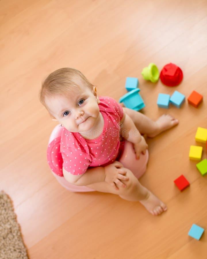 Babyzitting op kamerpot en het spelen met speelgoed Hoogste mening royalty-vrije stock afbeeldingen