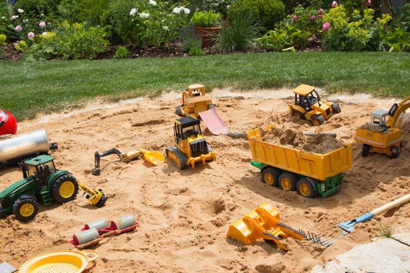 Bac à sable dans un jardin avec différentes choses de jeu de sable. image libre de droits