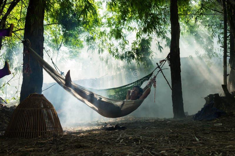 Bac Ninh, Vietnam - 29 mai 2016 : Un homme faisant une pause à midi sur l'hamac à la nuance de l'arbre par la rivière de Cau photographie stock