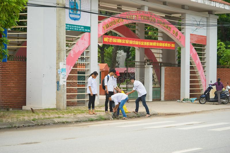 Bac Ninh, Vietnam - Sep 9, 2015: Group of high school students cleaning street in front of their school within the volunteer event. For saving environment stock photo