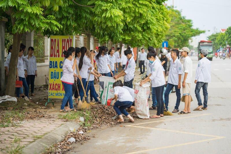 Bac Ninh Vietnam - September 9, 2015: Grupp av högstadiumstudenter som framme gör ren gatan av deras skola inom volontärhändelsen arkivfoto